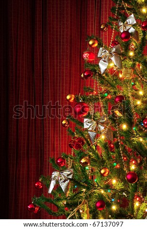 Photo of a Christmas tree next to red window curtains with copy space - stock photo