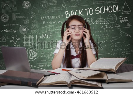 Photo of a confused schoolgirl studying with books and laptop computer on desk in the classroom