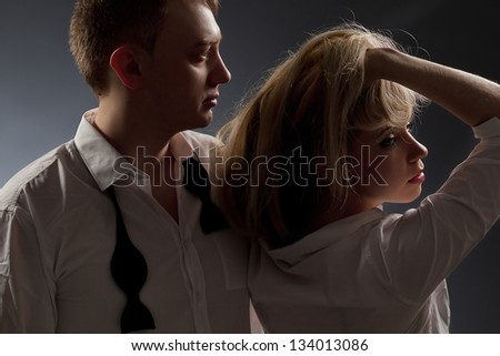 Photo of a couple in white shirt and black tie, the man holding sexy woman.