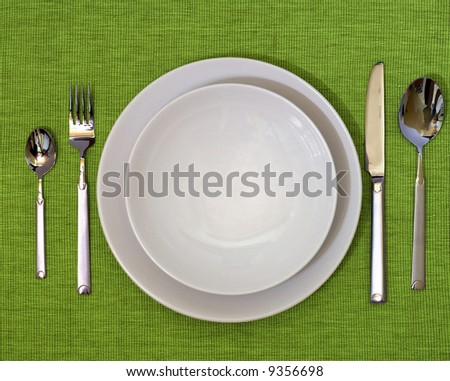 Photo of a dinner set on a green desk. - stock photo
