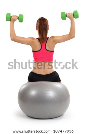Photo of a female from behind doing dumbbell shoulder press while sitting on an exercise ball.