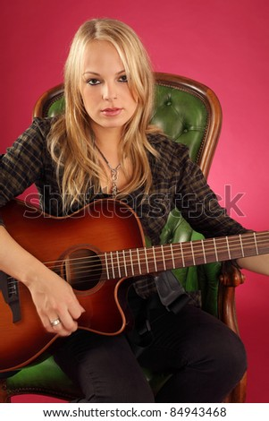 Photo of a female guitarist playing while sitting on a green leather chair.