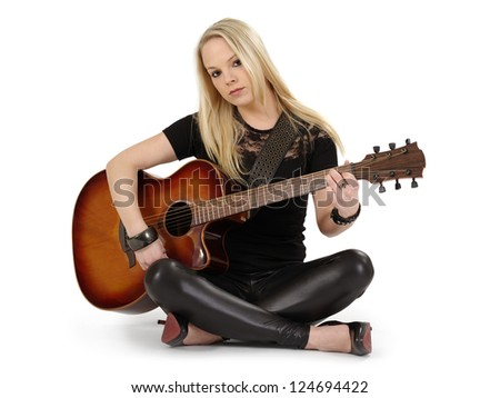 Photo of a female with long blond hair sitting on the floor playing an acoustic guitar.