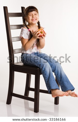 Photo of a girl with apple, sitting on a chair - stock photo