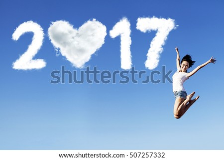 Photo of a joyful woman jumping on the blue sky with cloud shaped number 2017