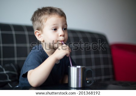 photo of a kid sipping juice while watching tv - stock photo