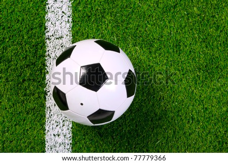 Photo of a leather football or soccer ball on a grass next to the white line, shot from above. - stock photo