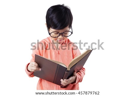 Photo of a little schoolgirl reading a book while wearing glasses in the studio, isolated on white background