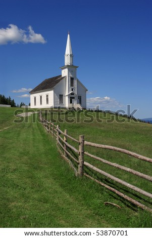 Photo of a little white wooden church in the countryside. - stock photo