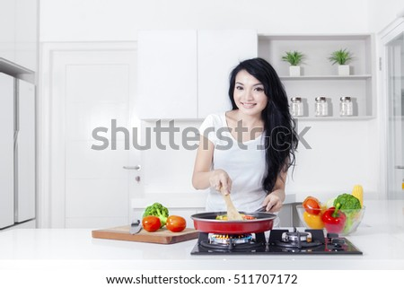 Photo of a lovely Asian woman smiling at the camera while cooking vegetable with a frying pan in the kitchen