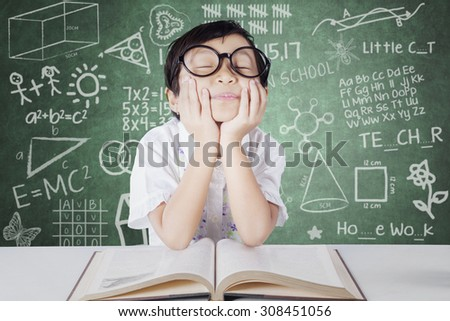 Photo of a lovely primary school student daydreaming in the classroom while wearing glasses