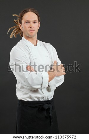 Photo of a male chef with dreadlocks, standing with his arms crossed over dark background.