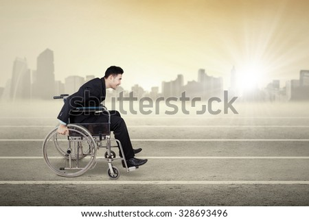 Photo of a male disabled entrepreneur pushing wheelchair on the race line - stock photo