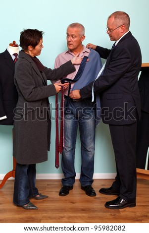 Photo of a man getting advice from his wife during a tailored bespoke suit fitting. - stock photo