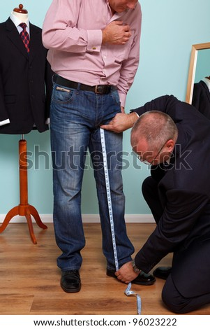 Photo of a man having his inside leg measured by a tailor during a bespoke suit fitting. - stock photo