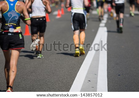 Photo of a marathon competition during an ironman. Focus on the foreground , no faces recognizable. Shallow depht of field. - stock photo