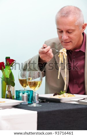 Photo of a mature man eating pasta in a restaurant. - stock photo