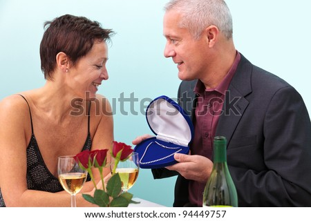 Photo of a mature man giving his wife a diamond necklace whilst sat at a table in a restaurant. - stock photo