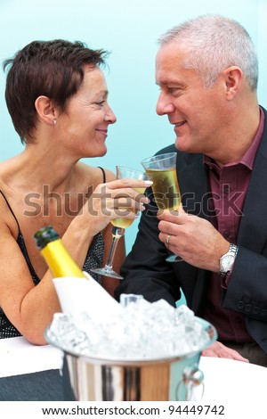 Photo of a mature married couple celebrating with a glass of champagne in a restaurant. - stock photo