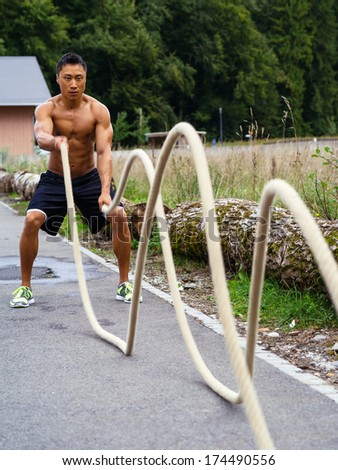Photo of a muscular Asian man outdoors working out with training ropes.  - stock photo