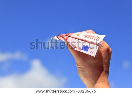 Photo of a paper plane made from a ten Euro banknote, isolated on a white background. - stock photo