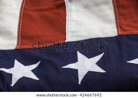 Photo of a part of the United State flag showing two stars, two white stripes and two red stripes.