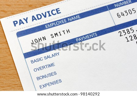 Photo of a payslip. The payslip is a mock up the names and all other information on it is fictional. - stock photo