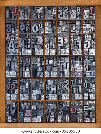 Photo of a printing tray full of old used metal letterpress in mixed fonts, all the letters of the alphabet and numbers from 0-9 mixed in with some punctuation marks and symbols. - stock photo