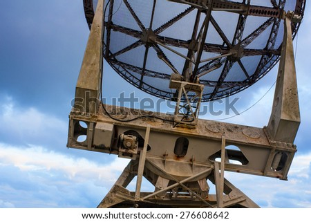 Photo of a radar/antenna against the dark and uneven sky - stock photo