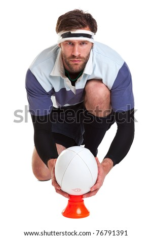 Photo of a rugby player placing the ball on a kicking tee, cut out on a white background. - stock photo