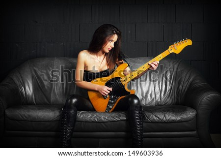Photo of a sexy female guitar player wearing leather boots and sitting on old leather couch.