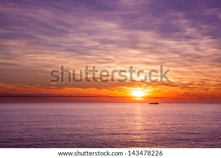 Photo of a ship sailing in the ocean at sunset