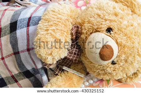 Photo of a sick teddy bear with a  bandage in bed - stock photo