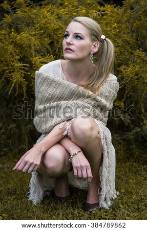 Photo of a sitting woman which looking serious into the nature