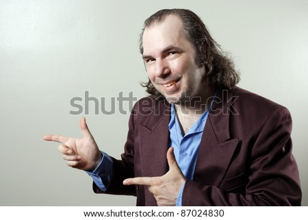 Photo of a sleazy salesman pointing at something. - stock photo
