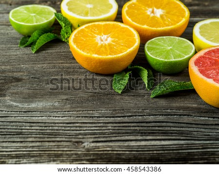 Photo of a sliced grapefruit, orange, lemon, lime, and mint leaves on a old rustic slab of barn board. - stock photo