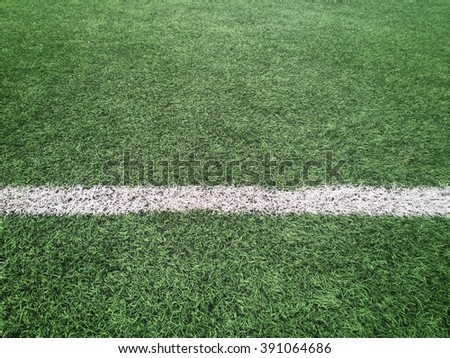 Photo of a sports or soccer fields grass with white line shot from above.