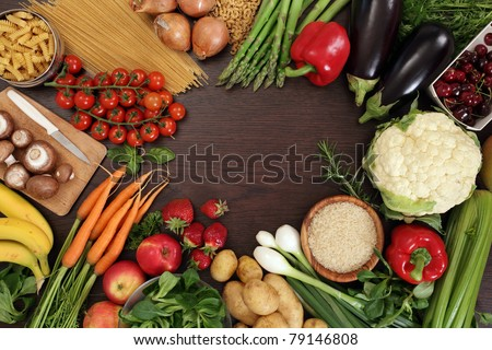 Photo of a table top full of fresh vegetables, fruit, and other healthy foods with a space in the middle for text. - stock photo