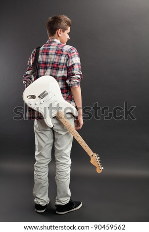 Photo of a teenage male standing with a white electric guitar slung over his back. - stock photo