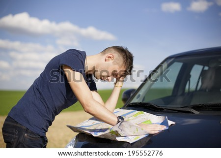 Photo of a traveler parked his car by the side of a  road,  lost and reading the map. Focus on the map and male. - stock photo