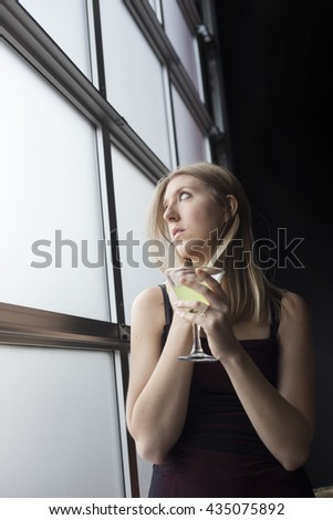 Photo of a very attractive blonde outside drinking a margarita from a martini glass and gazing out a window. - stock photo