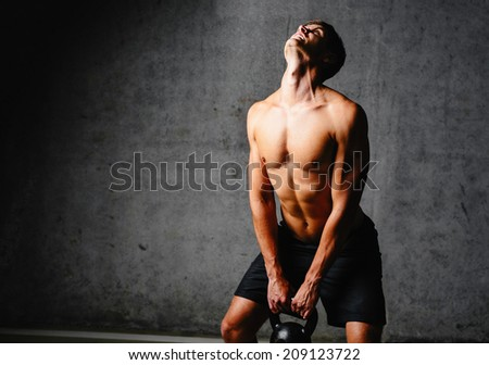 Photo of a weightlifter doing some repetitions with a kettlebell - stock photo