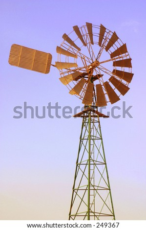 Photo of a windmill with a blue sky background.