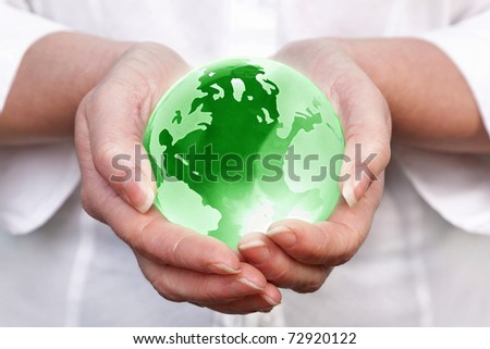 Photo of a woman holding a glass globe in her hands, concept image for worldwide and global related themes.