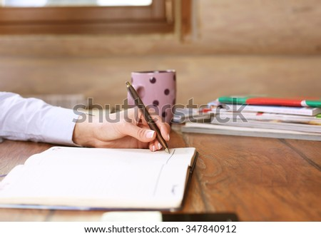 Photo of a woman holding a tablet with no name coffee cup and a stack of books in background on a wood table with shallow depth of field in wood house - stock photo