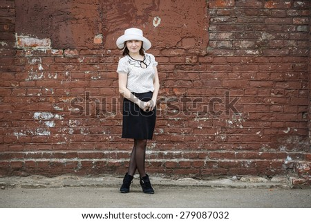 Photo of a woman in a white hat, blouse and black skirt, standing against the backdrop of an old vintage brown brick wall. Space for text. - stock photo