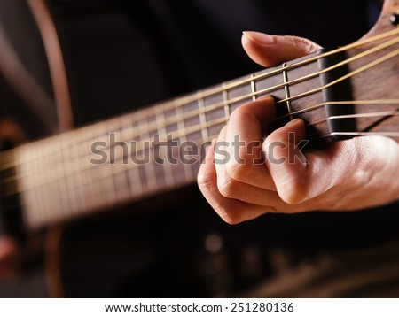 Photo of a woman playing an acoustic guitar with extreme shallow depth of field with focus on hand and headstock. - stock photo