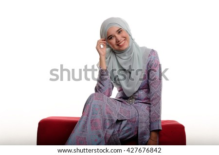 Photo of a young and beautiful muslim Malaysian lady wearing hijab and traditional malay costume known as songket smiling while sitting on red sofa on white background - stock photo