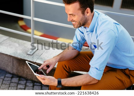 Photo of a young attractive man sitting outdoors and browsing the internet on a tablet - stock photo