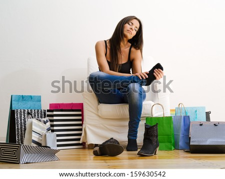 Photo of a young beautiful female sitting on a chair surrounded by shopping bags and rubbing her sore feet.  - stock photo
